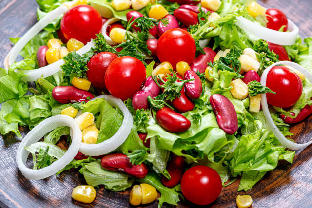 Close-up salad with beans, corn, tomatoes, lettuce, leeks and greens