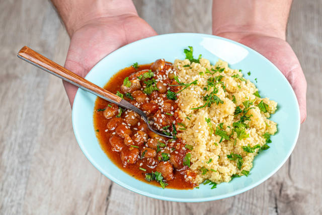 A plate of vegetarian lunch in the hands of a man. Beans in tomato sauce and couscous