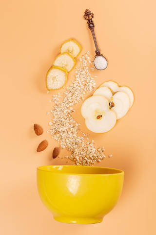 Sliced banana, apple, almond and oatmeal with a spoonful of sugar over an empty bowl