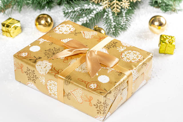 Golden gift with christmas tree branches and snow