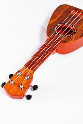 Toy Hawaiian guitar ukulele on white background