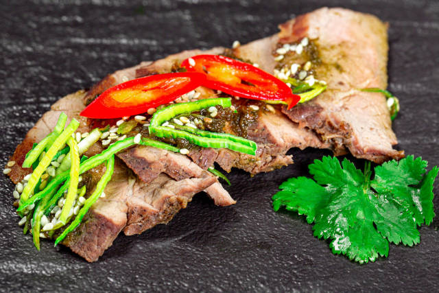 Close-up of baked beef with leek and hot chili pepper