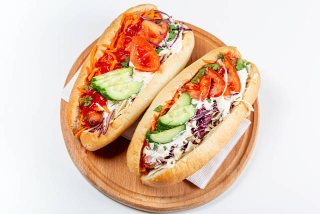 Top view, two hot dogs on a wooden kitchen board