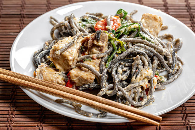 Noodles with cuttlefish ink in creamy sauce with tuna