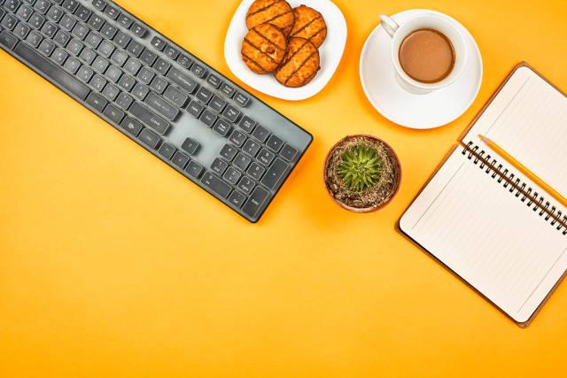 Coffee break. Pc keyboard, notepad, coffee cup and sweet cookies on yellow