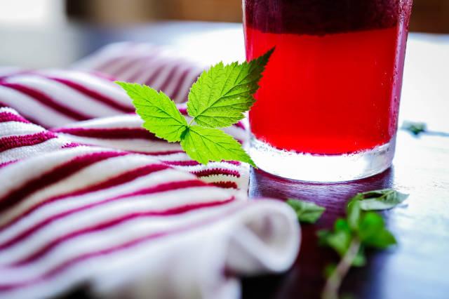 Green raspberry leaves beside refreshment