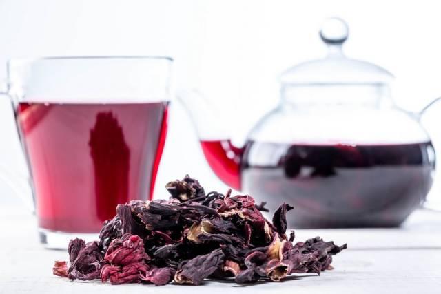 Nahaufnahme von getrocknetem Hibiskus und aufgebrühtem roten Tee in einem Glas und einer gläsernen Teekanne