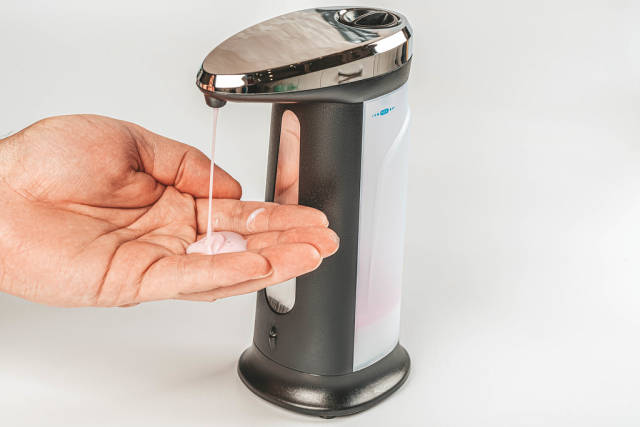 Close up of male hand uses automatic soap dispenser