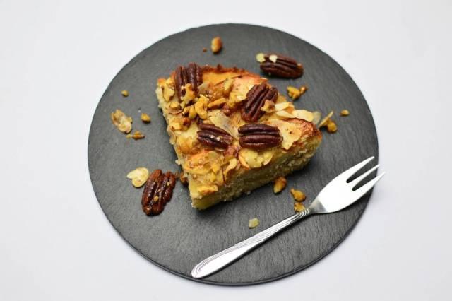 Apfel-Streuselkuchen mit Pecannüssen auf einer runden Schieferplatte mit Kuchengabel