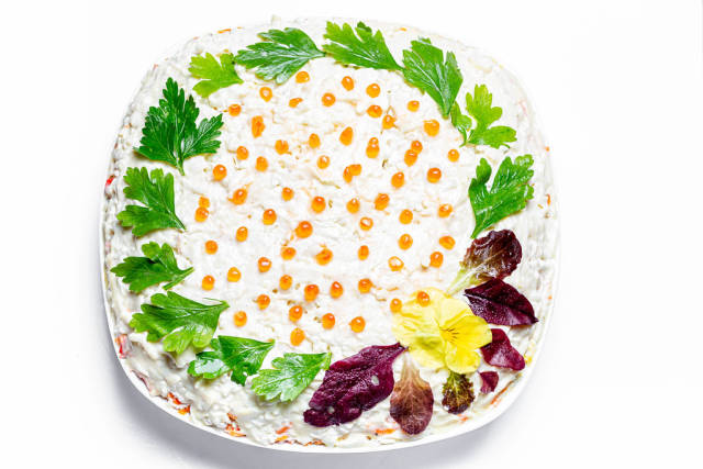 Salad with vegetables and crab sticks, decorated with fresh parsley and spinach leaves with red caviar