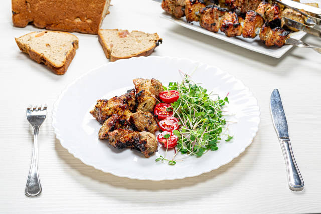 Shashlik with micro greens radish and tomato slices on a white wooden table with a knife and fork