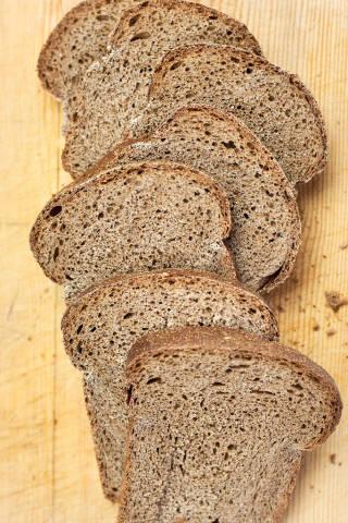Loaf of sliced wheat bread on cutting board