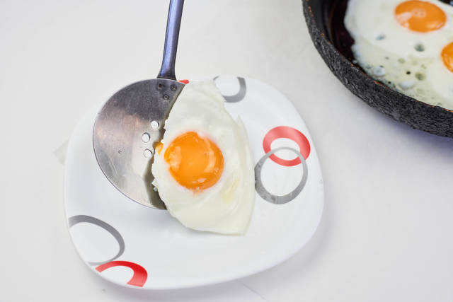 Putting a freshly fried sunny-up-side egg on the plate