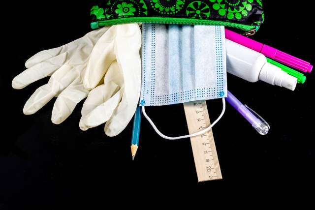 Open pencil case with school supplies, rubber gloves and mask on black background