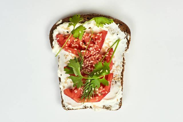 Bread slice with spread sour cream, tomato and parsley