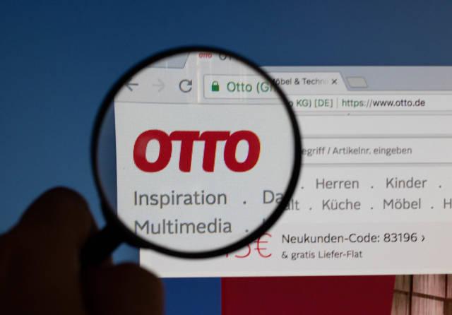 Otto-Logo am PC-Monitor, durch eine Lupe fotografiert