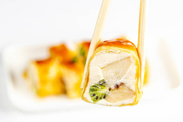 Chopsticks hold a dessert roll with cheese, Apple, kiwi and banana