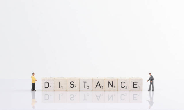 Two businessman standing next to Distance text on wooden blocks
