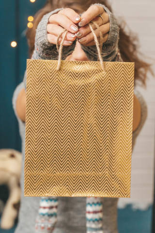Close-up, golden gift bag in female hands