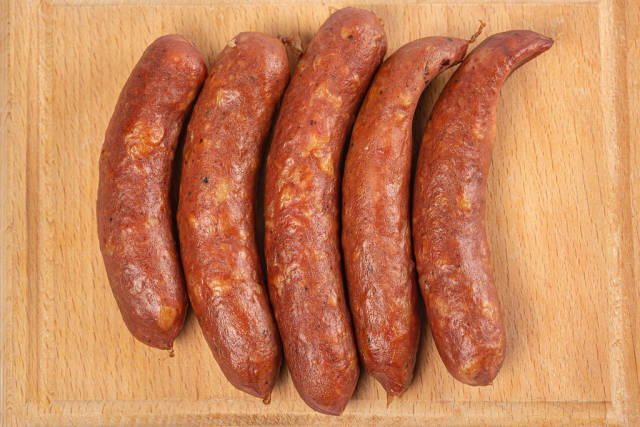 Smoked sausages on wooden kitchen board, top view