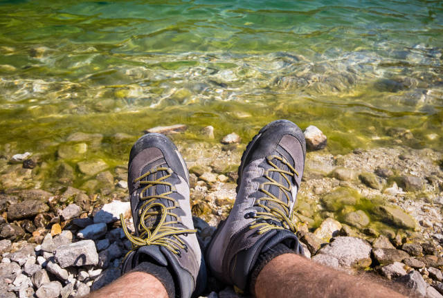 Man in hiking shoes sittng near the lake