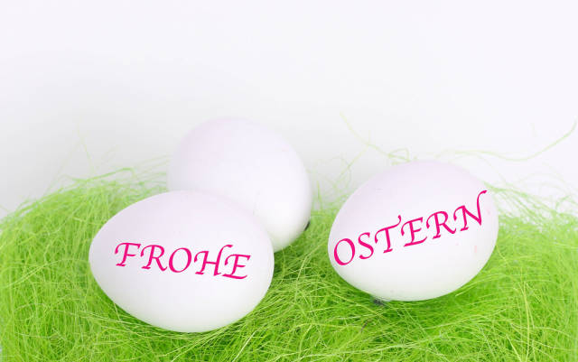 Easter eggs on green grass with Frohe Ostern text
