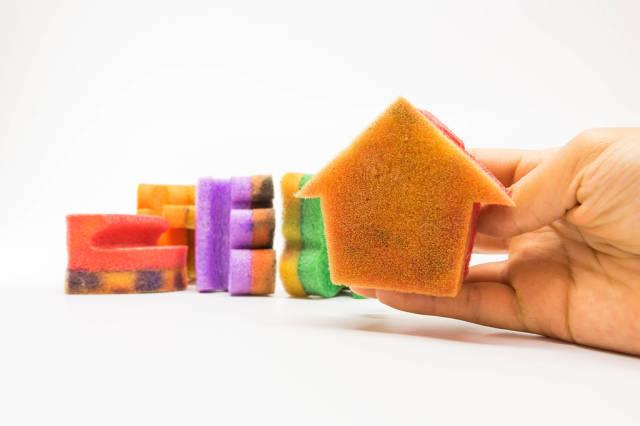 Hand holding a house shaped sponge