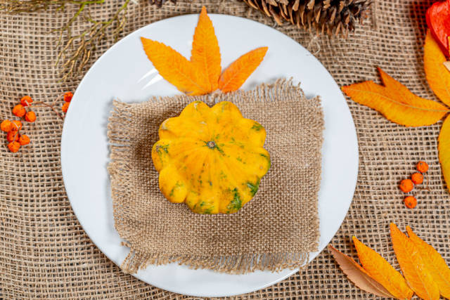 Pumpkin on a plate with autumn leaves, berries and cones. Autumn holidays background