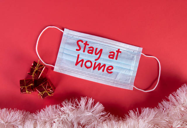 Medical protective face mask with Stay at Home text and Christmas decorations on red blue background