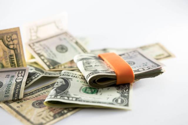Orange money band holding dollar bills