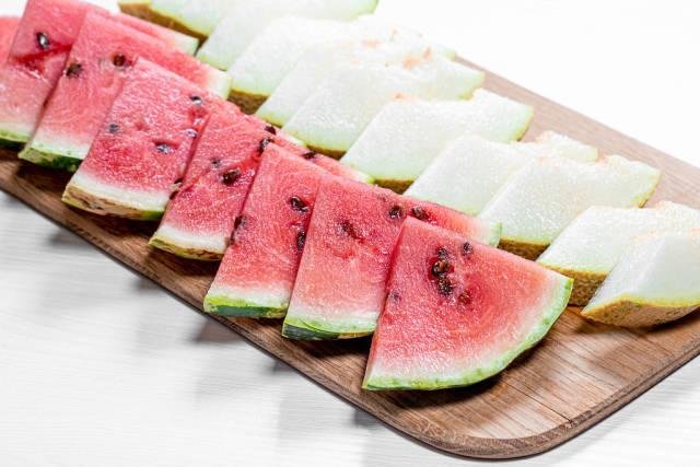 Cut triangular pieces of ripe watermelon and melon on kitchen Board