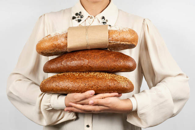 Woman holding a pile of breads