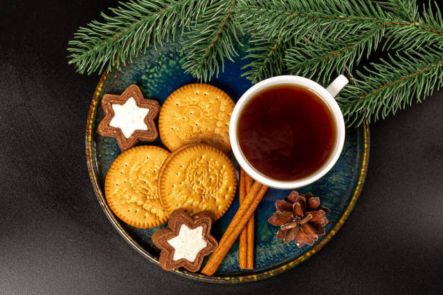 Top view, stars and round cookies with a cup of coffee and branches of a christmas tree