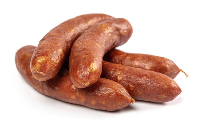 Small smoked sausages on white background