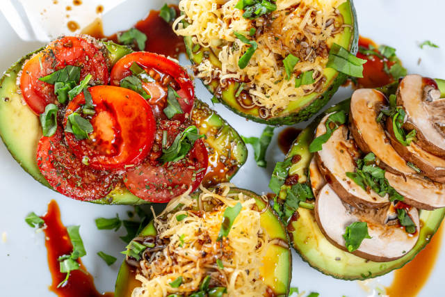 Avocado halves stuffed with mushrooms, cheese, tomatoes and herbs. Top view