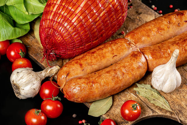 Sausages and ham with spices and tomatoes on a wooden board