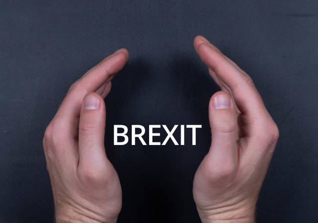 Brexit text with man hands on black bacground