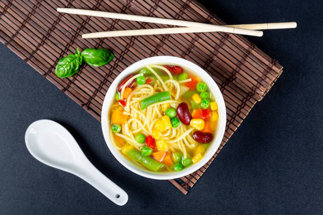 Top view, a bowl of vegetable soup with chopsticks and a spoon