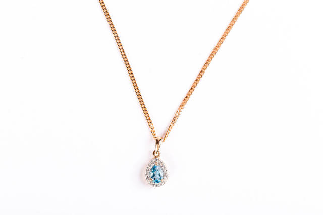Gold chain and pendant on white background