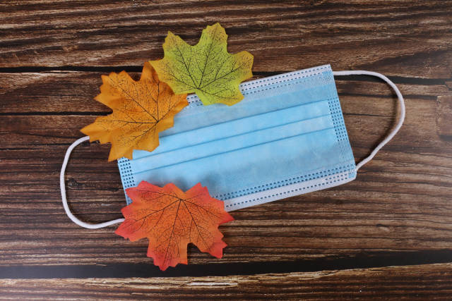 Medical face mask with autumn leaves on wooden background