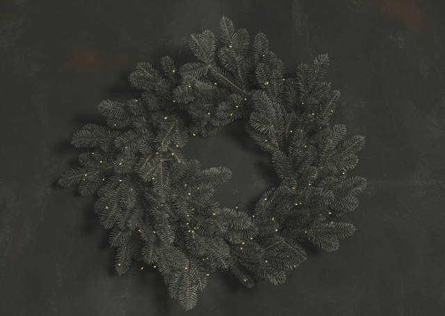 Wreath of branches of a christmas tree with a garland on a dark wall