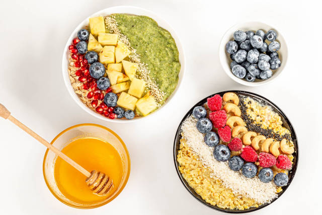 Top view, porridge with fresh berries, fruits, nuts, seeds and honey