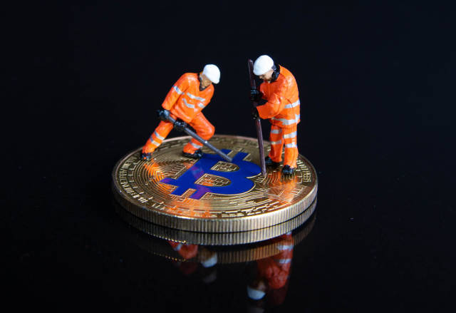 Miner figures working on a Bitcoin