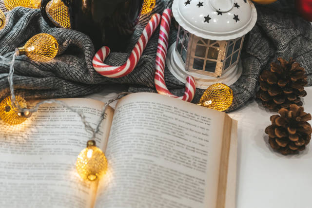 Christmas tale concept-open book with garland, lantern and candy lollipops