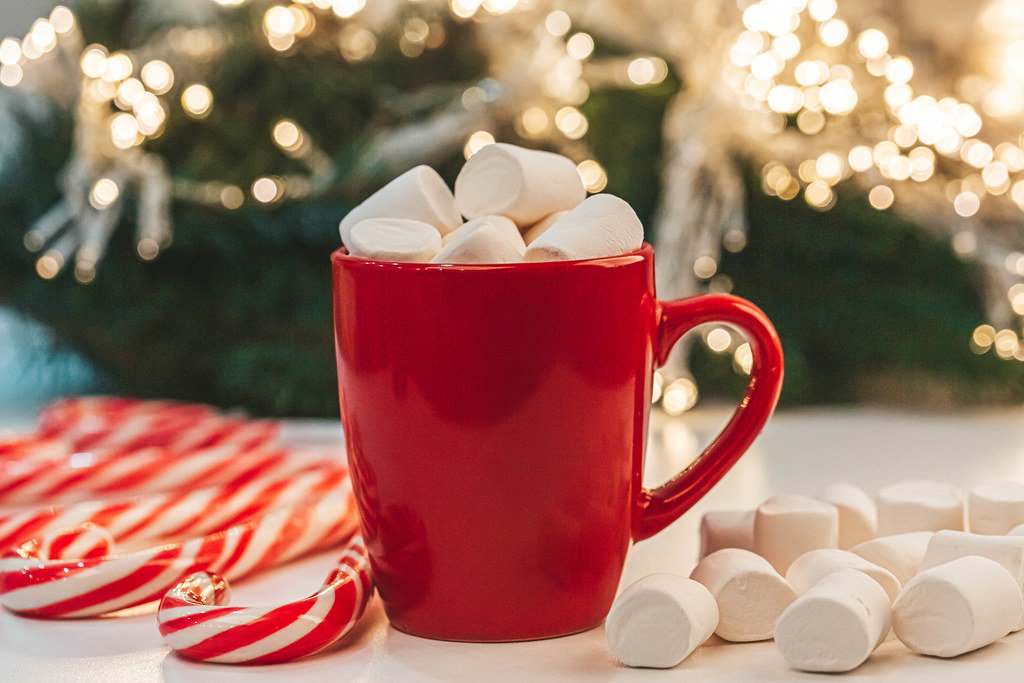 Red mug of cocoa with marshmallows on christmas background