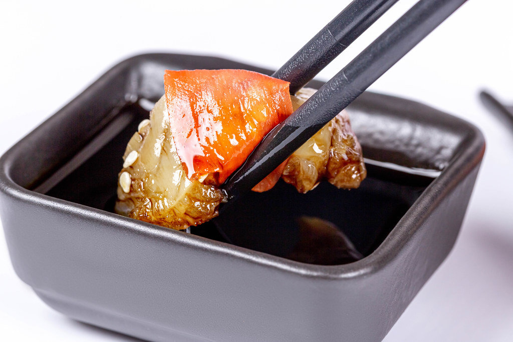 Close-up, sashimi with ginger is dipped in soy sauce