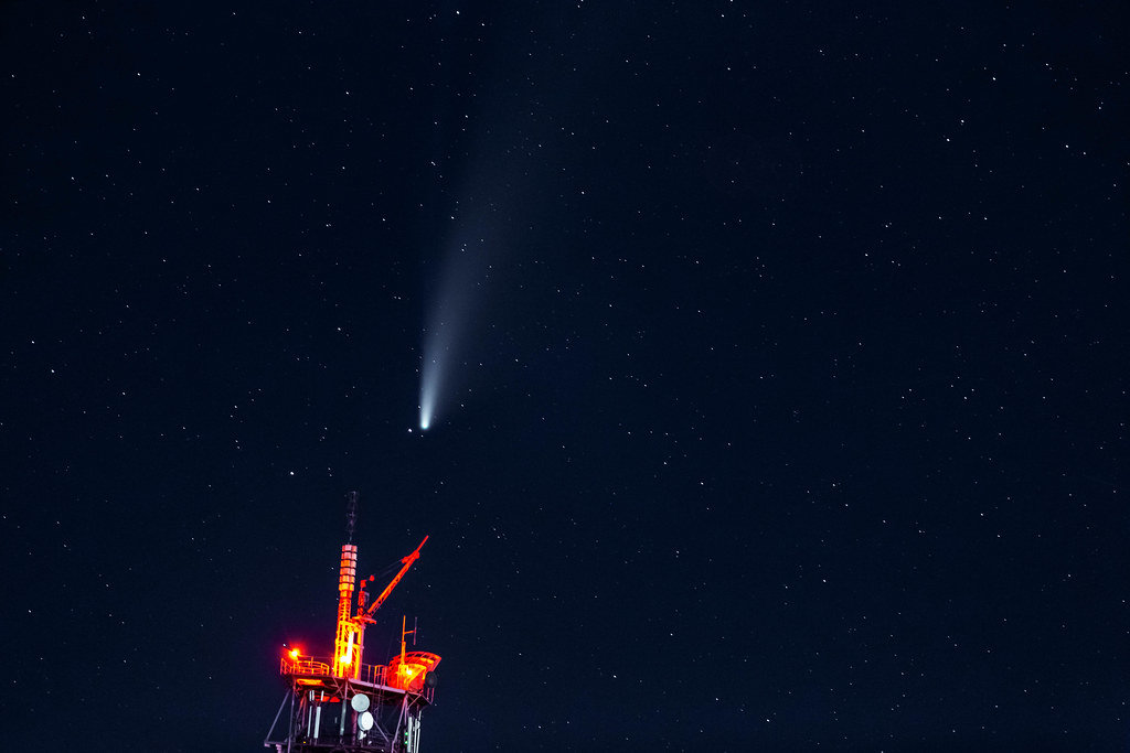 A comet with a large dusty glowing tail in the night sky. Comet Neowise over the TV tower