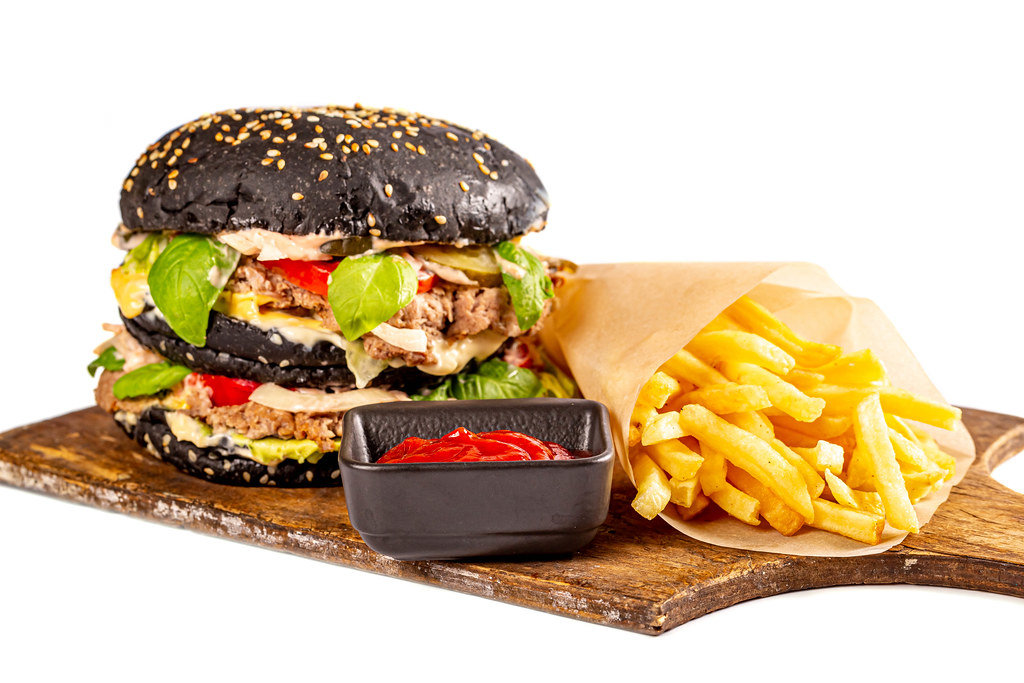 Black burger with meat cutlet and vegetables on a wooden board with french fries