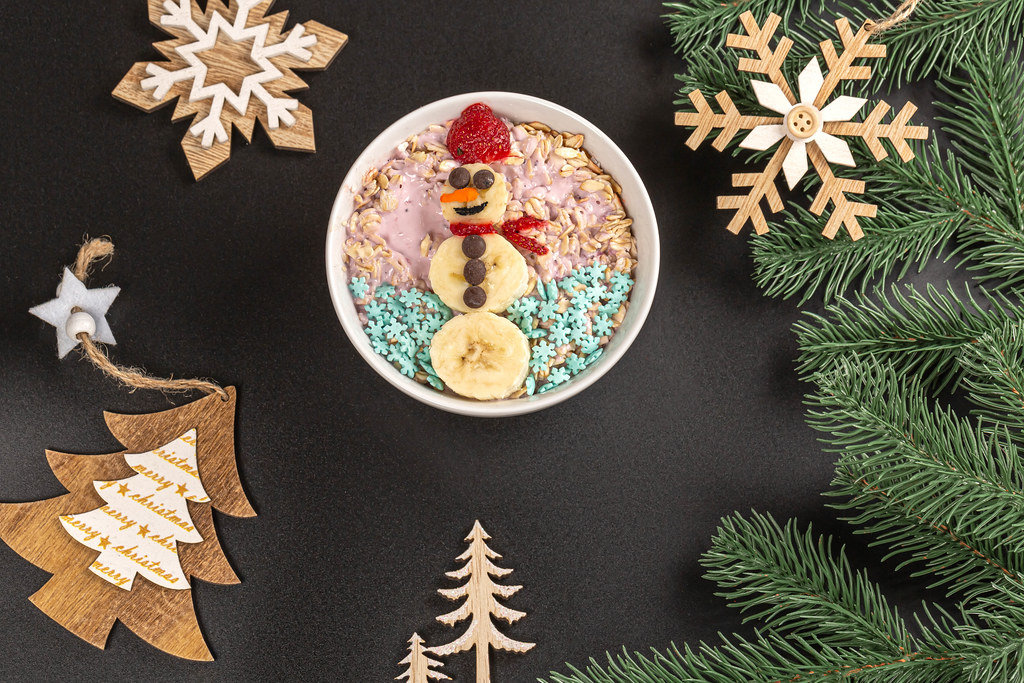 Oatmeal with yogurt and snowman made from slices of banana and strawberry on christmas background