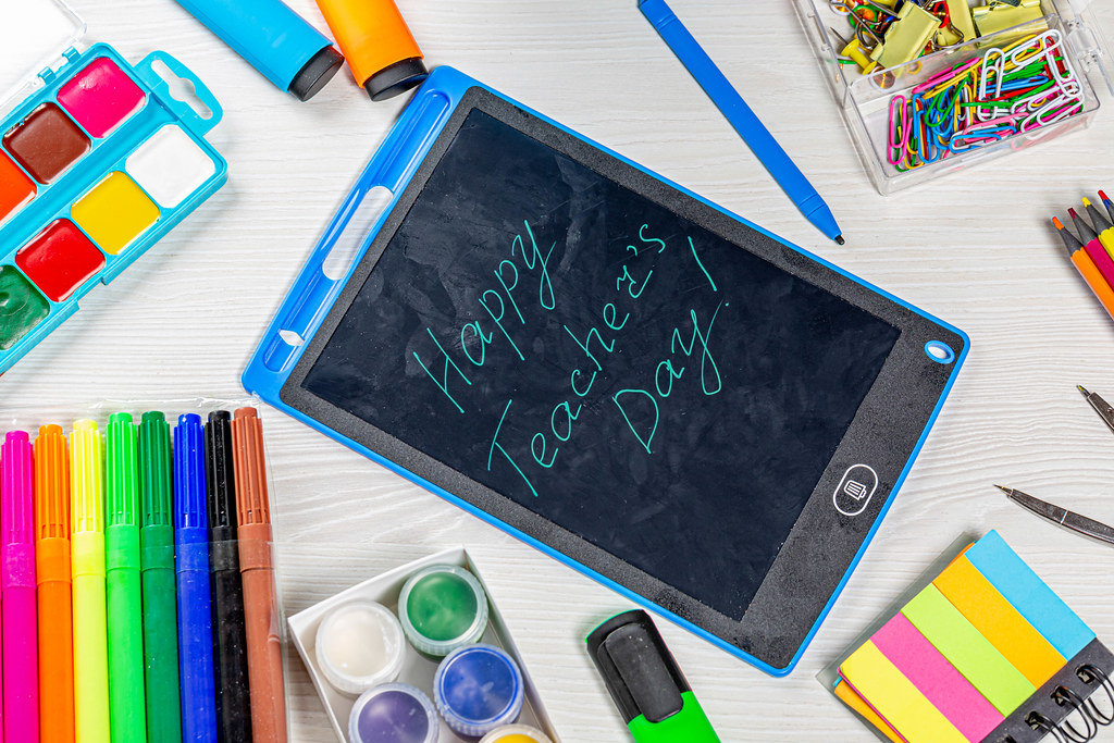 Happy Teachers Day inscription with markers, pencils, paper clips, paints and compasses on a white wooden table. Top view